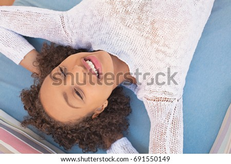 Over head beauty portrait of african american young woman smiling with joyful expression, laying relaxing on a home sofa, teenager. Black adolescent lifestyle and recreation, female lounging.
