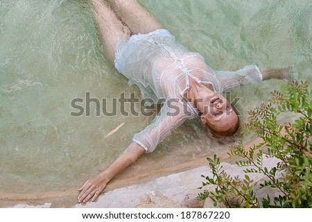 Over head beauty portrait view of a young woman relaxing in the transparent blue waters of a health spa natural swimming pool with her eyes shut, enjoying a summer holiday, outdoors healthy lifestyle.