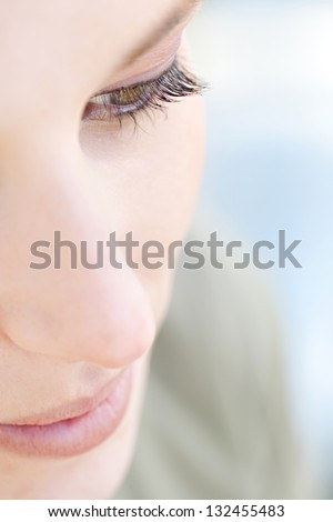 Over head close up beauty portrait of a young caucasian healthy woman face and eye looking down with long eyelashes.
