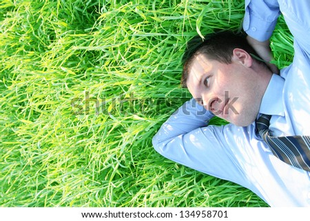 Over head close up portrait of a successful businessman laying down on green grass