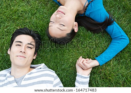 Over head close up portrait view of a young and attractive Japanese couple laying down on green grass and holding hands while relaxing together outdoors.