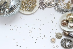 Over head flat lay New Years Eve party decorations and beauty/fashion products. Disco ball, star confetti, snowflake, glitter, party hat, makeup, jewelry and ornaments. Frame with room for copy.