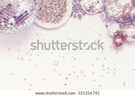 Over head flat lay New Years Eve party decorations. Silver and gold metallic colors. Disco ball, star confetti, snowflake, glitter, party hat, and a bowl of baubles. Frame with room for copy.