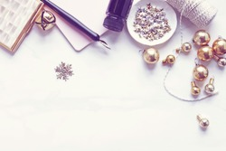 Over head flat lay view of a chic pink and gold Christmas desktop. Jingle bell, snowflake, twine, stars, pen and ink,pink notebook and vintage ornaments.