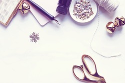 Over head flat lay view of a chic pink and gold winter Christmas desktop.  Snowflake, jingle bells, stars, twine, pen and ink, pink notebook and gold scissors.