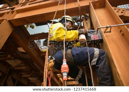 Over head picture of Male rope access electrician abseiler wearing safety harness, helmet using two rope abseiling drilling metal structure with magnet mine site, Perth, Australia