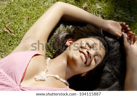 Over head portrait of a young indian woman laying down on green grass in the park, smiling.