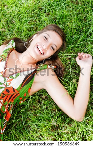 Over head portrait view of an attractive young woman laying down on textured green grass listening to music with her mp3 player and smiling joyfully during a summer day outdoors.