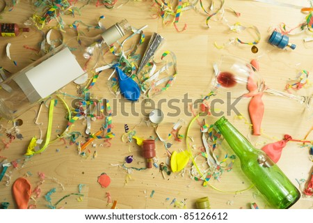 Over head shot of a wooden floor after a party celebration with empty bottles,wine glass and party decorations,