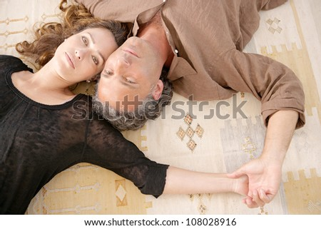 Over head view of a mature couple laying down on carpet at home.