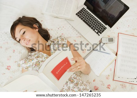 Over head view of a teenager student of languages doing her homework, laying on her bed in her bedroom with a laptop computer and cell phone, reading an open Spanish book.