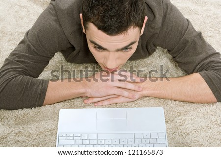 Over head view of a young hispanic man laying down on a furry carpet at home, using his laptop computer.