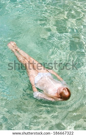 Over head view of a young woman swimming in the clear blue waters of a health spa swimming pool, relaxing on a summer holiday trip and enjoying a swim during a sunny summer day, outdoors lifestyle.