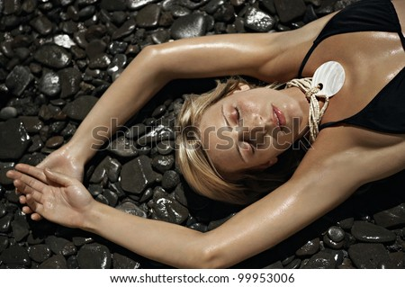 Over head view of a young woman wearing a black bikini and laying down on wet black stones with her eyes closed.