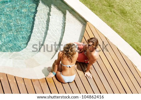 Over head view of an attractive couple sunbathing and being affectionate while sitting by a swimming pool's steps in a hotel's garden.