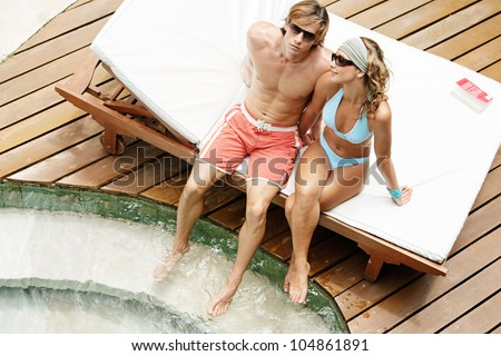 Over head view of an attractive couple sunbathing and wearing sunglasses while sharing a sun bed by a swimming pool.