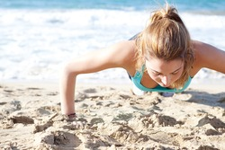 Over head view of an attractive young woman doing push ups exercises on the beach, keeping fit during a sunny day.
