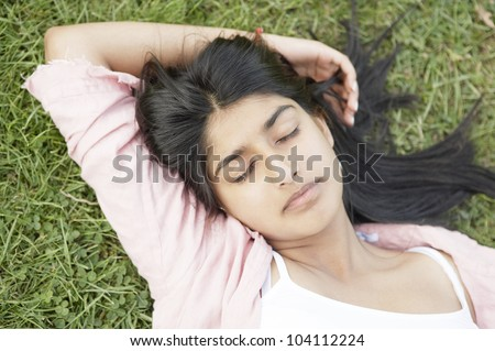 Over head view of an indian girl laying down on green grass with her eyes closed.