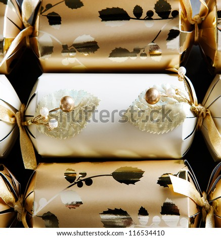 Over head view of three golden christmas crackers decorated with beads and ribbons against a black background.