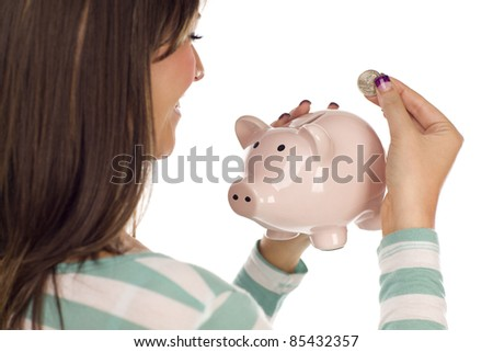 Over Shoulder of a Pretty Smiling Ethnic Female Putting a Coin Into Her Pink Piggy Bank Isolated on a White Background. - stock photo