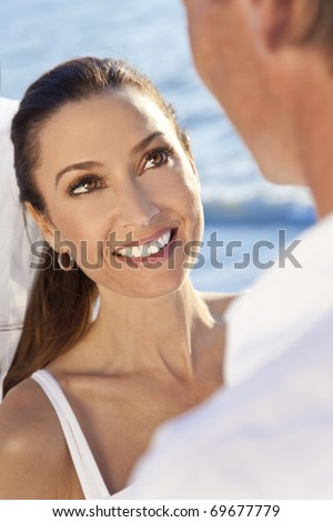 Over shoulder photograph of a smiling bride looking at the groom  in a married couple on a beautiful sunny tropical beach