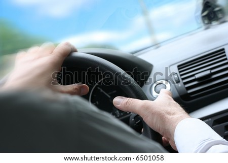 Over shoulder view of a man driving a car with his hands on the steering wheel, turning quick. (sunny weather)