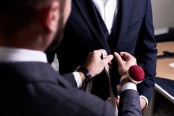 Over shoulder view of bearded fashion designer fitting bespoke suit to model, close-up shot