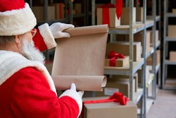 Over shoulder view of old Santa Claus wearing costume reading blank empty wish list standing in workshop gifts warehouse. Merry Christmas wishlist presents parcels post shipping delivery concept.