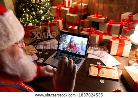 Over shoulder view of Santa Claus video calling kid girl on laptop greeting child by webcam talk open Christmas gift box by virtual online videocall using computer sit at workshop table on xmas eve.