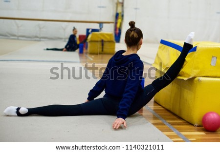 Over-split by Rhythmic Gymnast, with reflection in a back ground. Stretching, flexibility.
