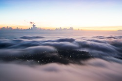 over the city, an aerial photo before dawn, clouds and lights of an early city