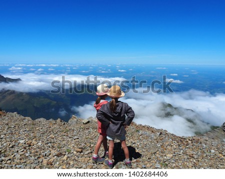 Over the clouds. Children watch the landscape during a break during the ascent of the Pic du Midi in the Pyrenees