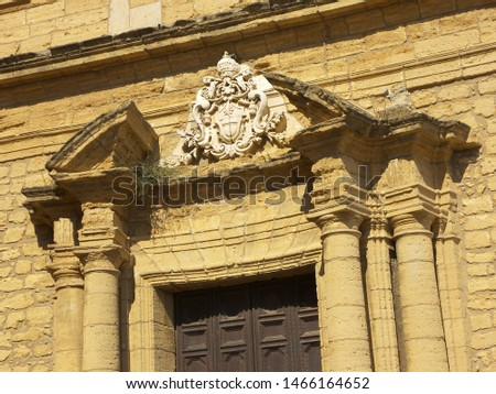 Over the door of the San Pietro church there is an emblem. The emblem is made of white marble. Four columns are close to the door. San Pietro is an old church in the center of Agrigento. #1466164652