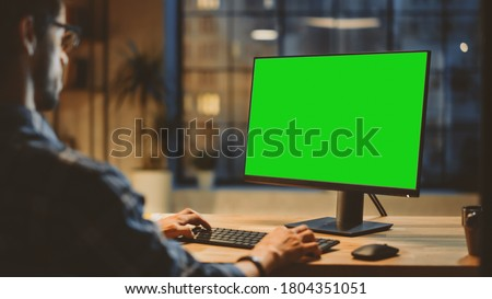 Over the Shoulder: Creative Young Man Sitting at His Desk Using Desktop Computer with Mock-up Green Screen. Evening in the Stylish Office Studio with City Window View