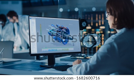 Over the Shoulder Shot: Female IT Scientist Uses Computer Showing CAD Software with Airplane Engine. In the Background Technology Development Laboratory with Scientists, Engineers Working