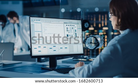 Over the Shoulder Shot: Female IT Scientist Uses Computer Showing System Monitoring and Controlling Program. In the Background Technology Development Laboratory with Scientists, Engineers Working