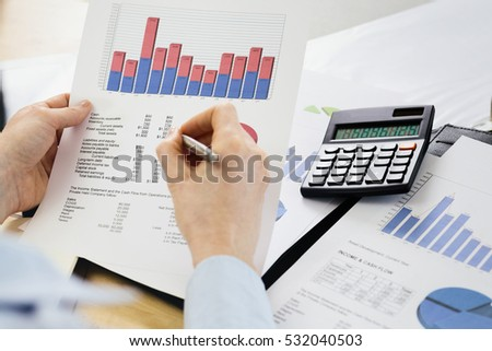 Over the shoulder shot of a businesswoman reading a cash flow report. Shallow DOF, focus on the paperwork.