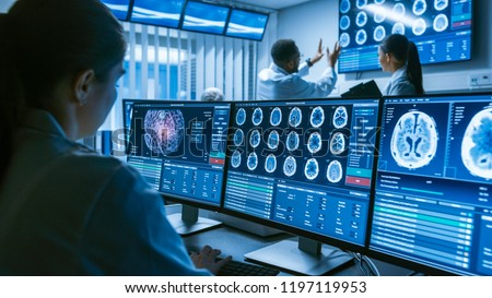 Over the Shoulder Shot of Female Medical Scientist Working with Brain Scan Images on a Personal Computer in Laboratory. Neurological Research Center Working on Curing Brain Tumors.