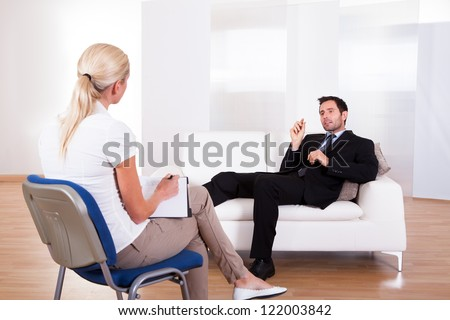 Over the shoulder view of a business man reclining comfortably on a couch talking to his psychiatrist explaining something
