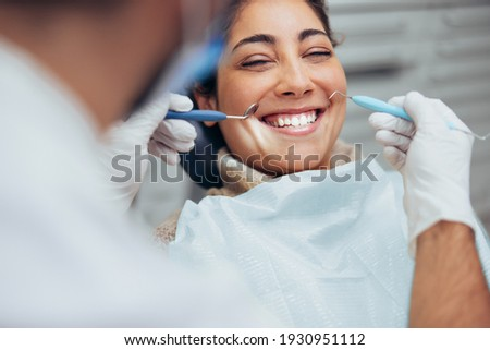 Over the shoulder view of a dentist examining a patients teeth in dental clinic. Female having her teeth examined by a dentist. Stockfoto ©