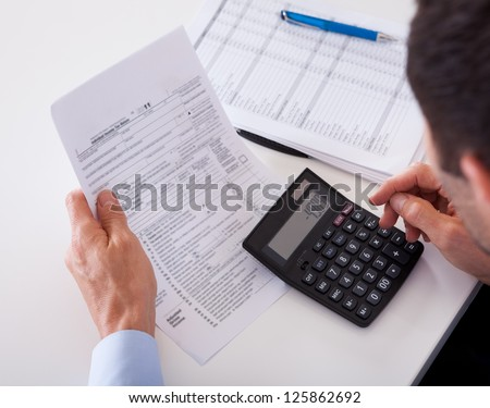 Over the shoulder view of a man checking an invoice on a calculator