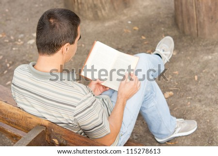 Over the shoulder view of a man in casual clothing sitting on a bench reading a book looking down onto the open pages