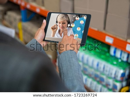 Over the shoulder view of a mixed race woman using a digital tablet for a video call in a warehouse. Public health social distancing and self isolation in quarantine lockdown concept digital