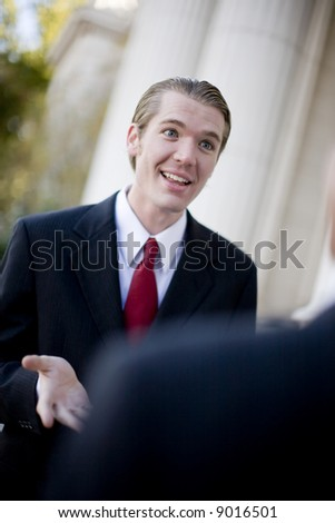 over the shoulder view of businessman standing in front of another businessman explaining something - stock photo