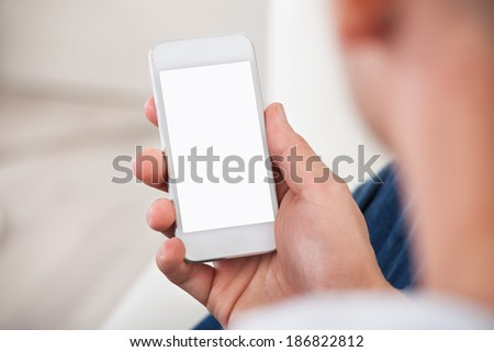 Over the shoulder view of the blank screen on a smartphone or mobile phone held in a mans hand