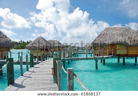 over water bungalow and the turquoise color lagoon - stock photo