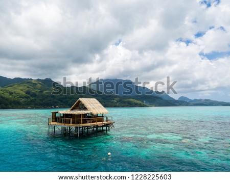 Over water bungalow of black pearl farmers. Blue azure turquoise lagoon with corals. Emerald Raiatea island, Leeward / Society islands, French Polynesia, Oceania, South Pacific Ocean near Tahiti.