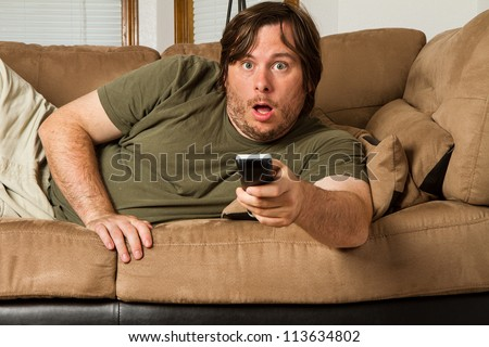 Over weight man watching something shocking on TV. Could it be tabloids, celebrity gossip, a movie, or something else?