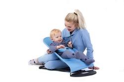 Over white background happy mom with her baby. One-year-old boy in a baby lounger with a young beautiful mother.