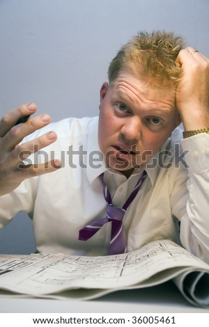 Over worked man looking at house plans - stock photo